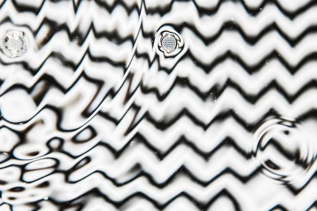 Varios tamaños de gota de agua sobre una superficie de piscina en blanco y negro