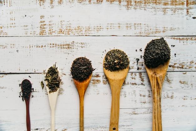 Varios té de hierbas en una cuchara de madera sobre la mesa