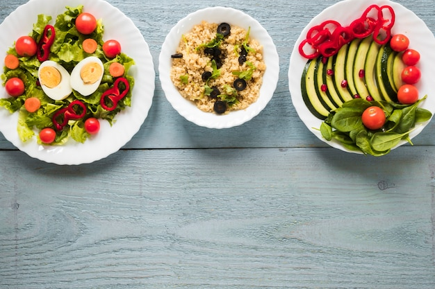 Varios tipos de alimentos saludables con huevo cocido y vegetales frescos dispuestos en una fila.
