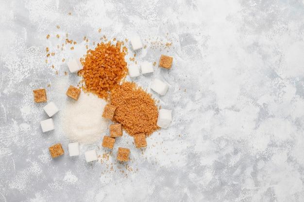 Varios tipos de azúcar, azúcar moreno y blanco sobre hormigón, vista superior