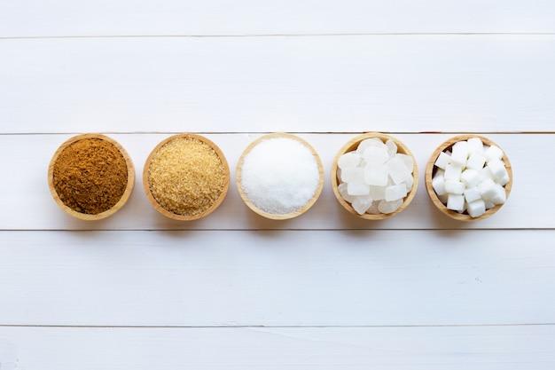 Varios tipos de azúcar en madera blanca