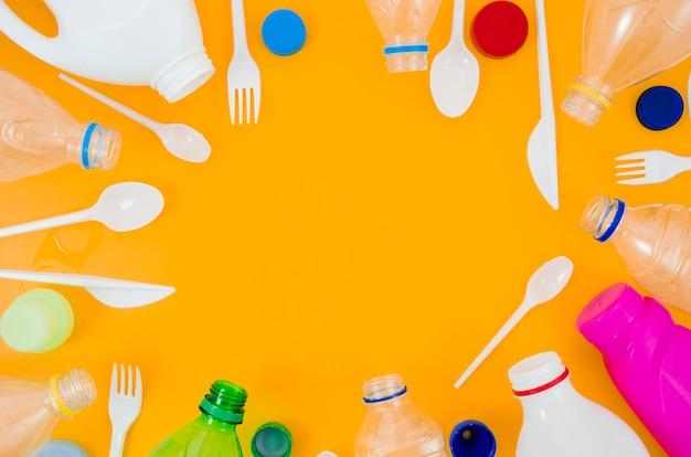 Varios tipos de botellas y cucharas dispuestas en un marco circular sobre fondo amarillo.