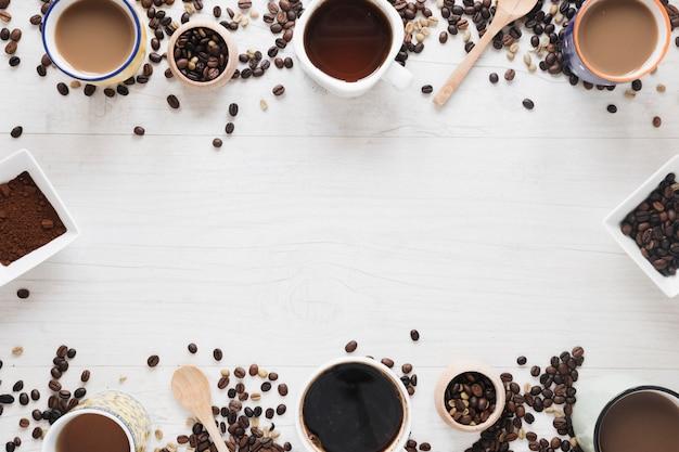 Varios tipos de café; granos de café crudos; café tostado en grano; café en polvo dispuesto en mesa blanca