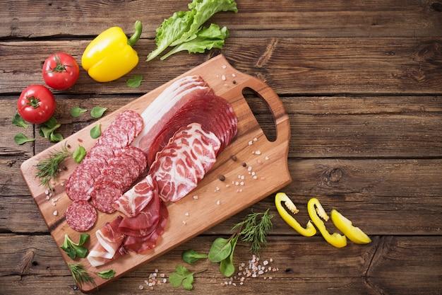 Varios tipos de carne y verduras en la mesa de madera.