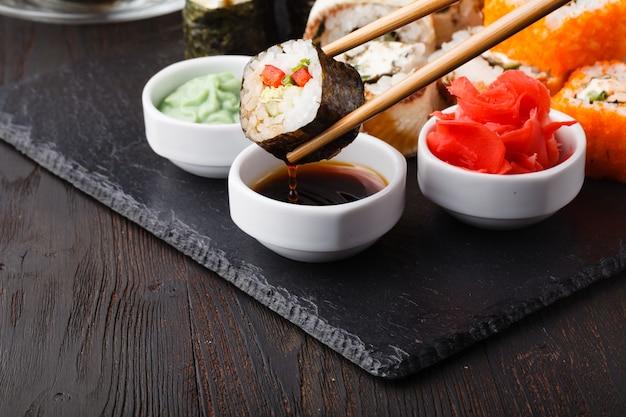 Varios tipos de comida de sushi servida en piedra negra