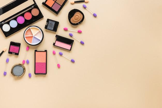 Varios tipos de cosméticos esparcidos sobre mesa beige.
