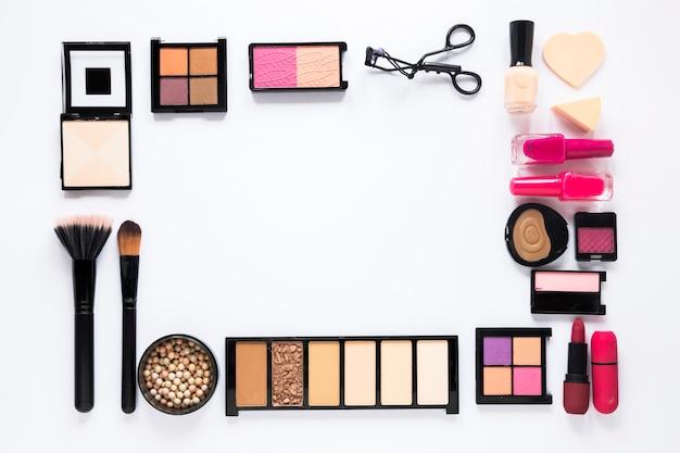 Varios tipos de cosméticos esparcidos sobre mesa blanca.