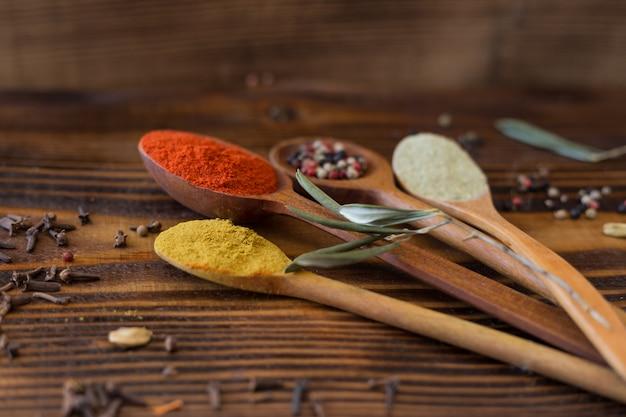 Varios tipos de especias en cuchara de madera
