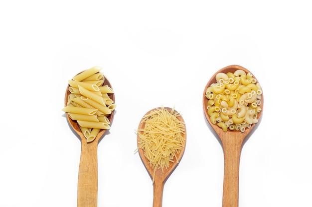 Varios tipos de macarrones en cucharas de madera sobre blanco