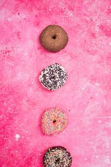 Varios tipos de macarrones sobre el fondo texturizado rosa