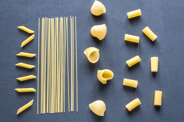 Varios tipos de pasta en la mesa oscura.