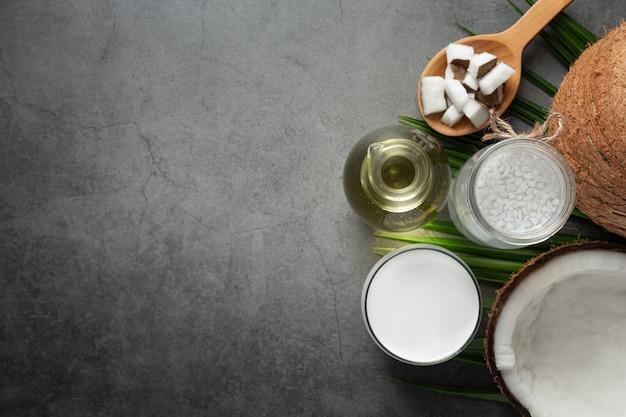 Varios tipos de productos de coco puestos en suelo oscuro.