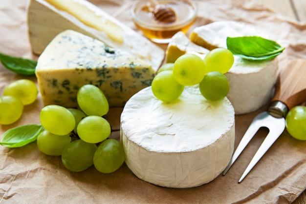 Varios tipos de queso, albahaca y uvas en una mesa