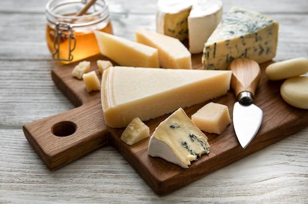 Varios tipos de queso en una mesa de madera blanca