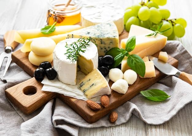 Varios tipos de queso sobre un fondo de madera blanca