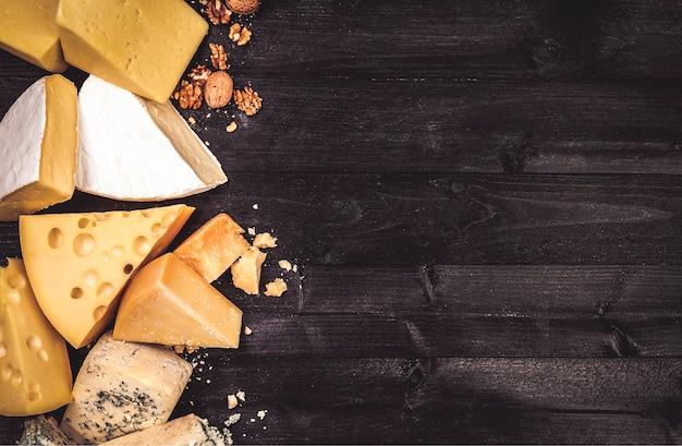 Varios tipos de queso sobre fondo de madera negra con espacio de copia