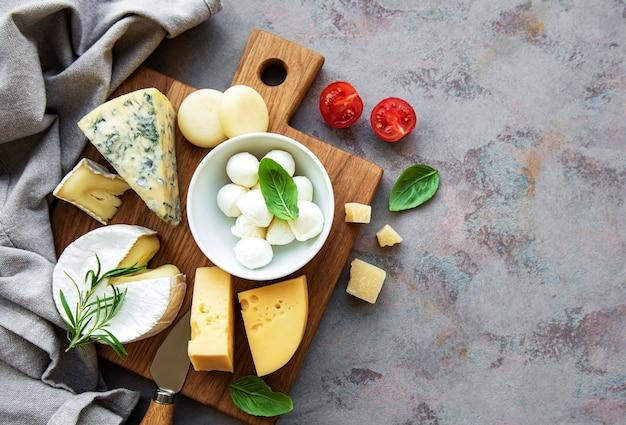 Varios tipos de queso, uvas y bocadillos en un hormigón gris