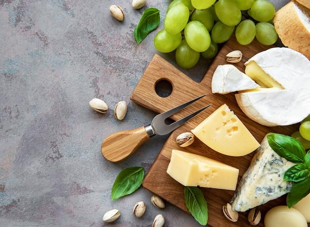 Varios tipos de queso, uvas y bocadillos en una mesa de hormigón gris