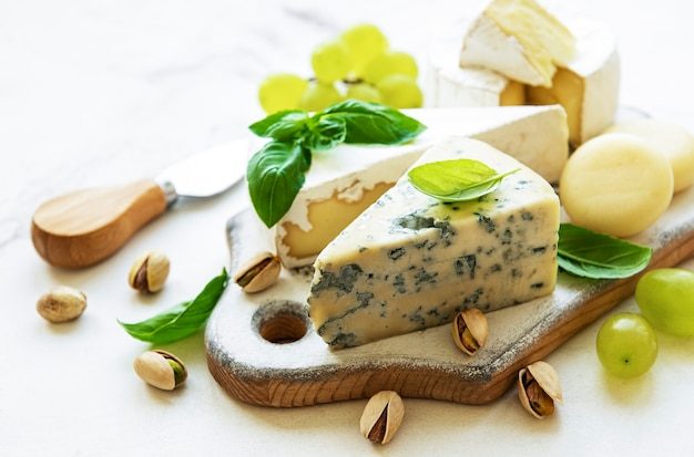 Varios tipos de queso, uvas y bocadillos en una mesa de mármol blanco