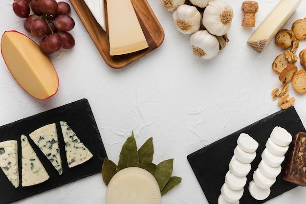 Varios tipos de queso con uvas sabrosas e ingredientes sobre fondo blanco
