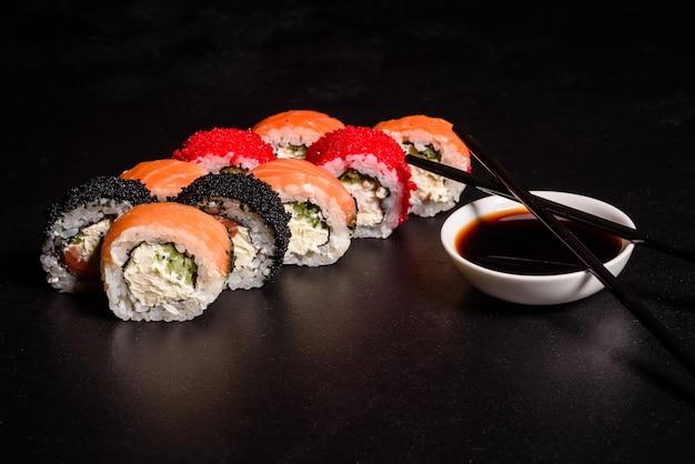 Varios tipos de sushi servido en un oscuro. rodillo con salmón, aguacate, pepino. menú de sushi comida japonesa.