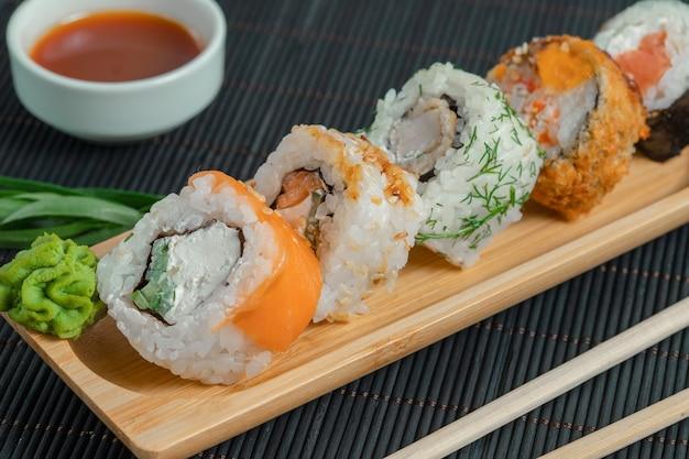 Varios tipos de sushi sobre tabla de madera con salsa.