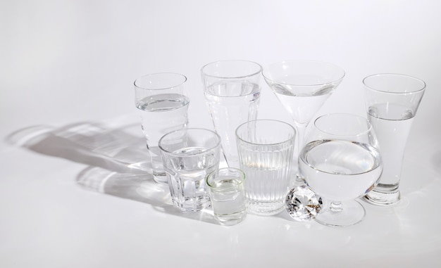 Varios tipos de vasos con agua pura aislado sobre fondo blanco