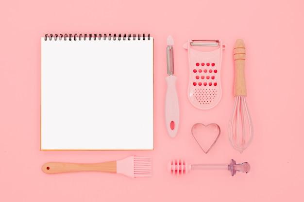 Varios utensilios de cocina rosa sobre fondo rosa abstracto. mayor, batir y planchar forma de cocción. vista horizontal superior copyspace amor cookong concepto