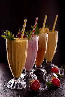 Varios vasos con papas fritas refrescantes con plátano, fresa y papaya, con hielo con tubo de cóctel sobre fondo negro