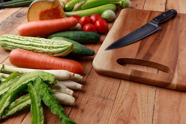Varios vegetales e ingredientes con cuchillo y tabla de cortar