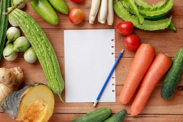Varios vegetales, especias e ingredientes con una hoja de papel.