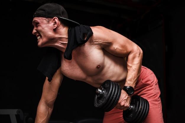 El varón adulto hermoso joven que hace pesas de un brazo rema en banco en gimnasio.
