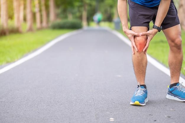 Varón adulto joven con dolor muscular durante la carrera. el corredor tiene dolor de rodilla debido a la rodilla del corredor o al síndrome de dolor patelofemoral, osteoartritis y tendinitis rotuliana. lesiones deportivas y concepto médico