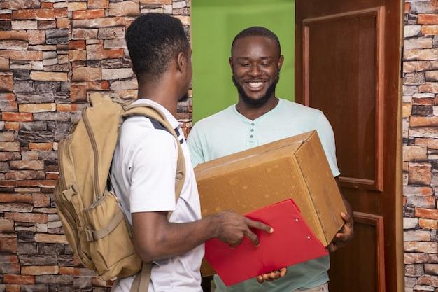 Varón africano recibiendo un paquete de un trabajador de servicio de entrega