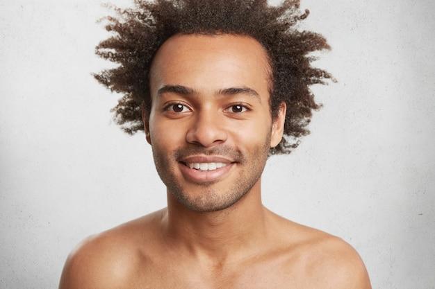 Varón afroamericano positivo desnudo con piel oscura y saludable y cabello rizado, sonríe suavemente