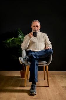 Varón anciano con bebida caliente cerca de la planta en maceta