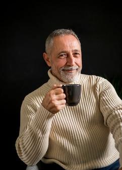 Varón anciano sonriente con bebida caliente
