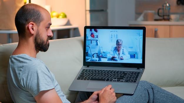 Varón caucásico charlando con el médico durante la consulta de telemedicina en línea