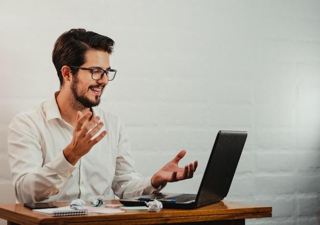 Varón caucásico joven que tiene una videollamada mientras trabaja en la oficina