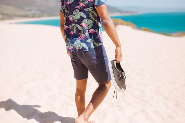 Varón de la cosecha caminando descalzo en la playa de arena