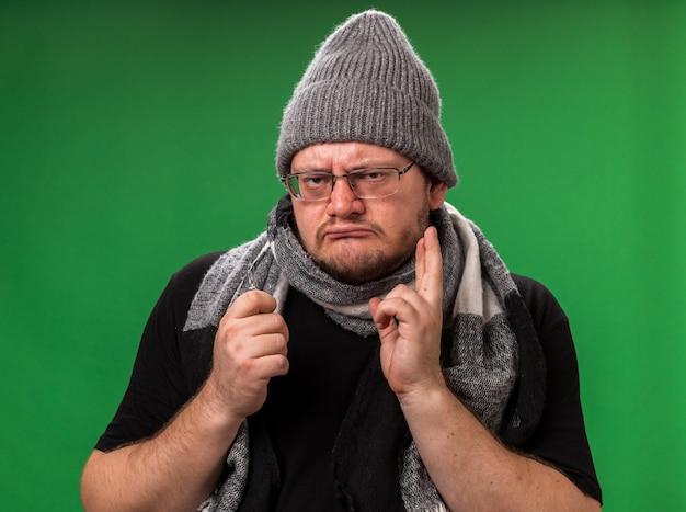 Varón enfermo de mediana edad con gorro de invierno y bufanda aislado en la pared verde