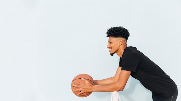 Varón étnico alegre que se inclina en la cerca que sostiene baloncesto