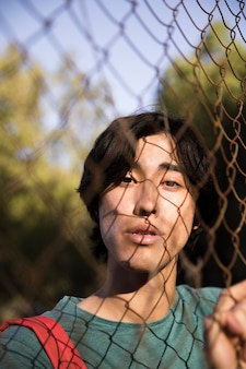 Varón étnico joven que mira la cámara a través de la cerca de alambre