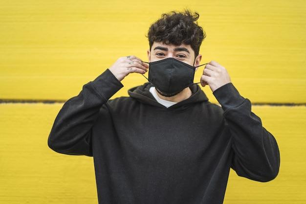 Varón europeo joven que llevaba una mascarilla en la pared amarilla vibrante