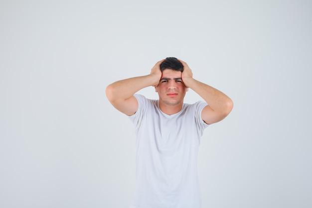 Varón joven agarrando la cabeza con las manos en camiseta y mirando olvidadizo, vista frontal.