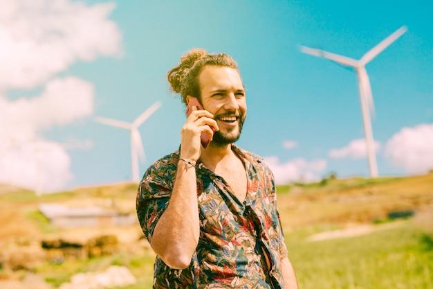 Varón joven alegre que habla en el teléfono móvil en la naturaleza