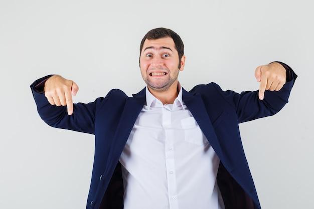 Varón joven apuntando hacia abajo en camisa, chaqueta y mirando alegre
