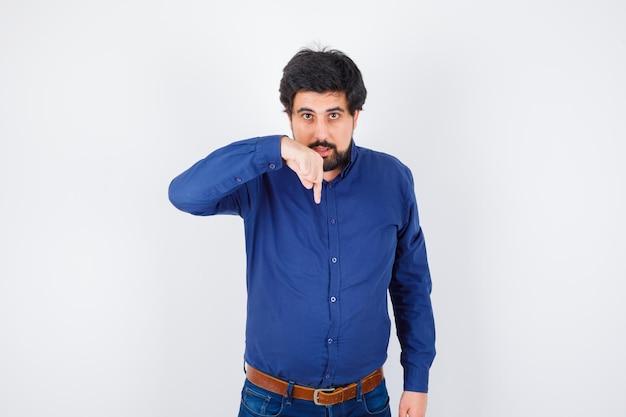 Varón joven apuntando hacia abajo en camisa, jeans y mirando serio, vista frontal.
