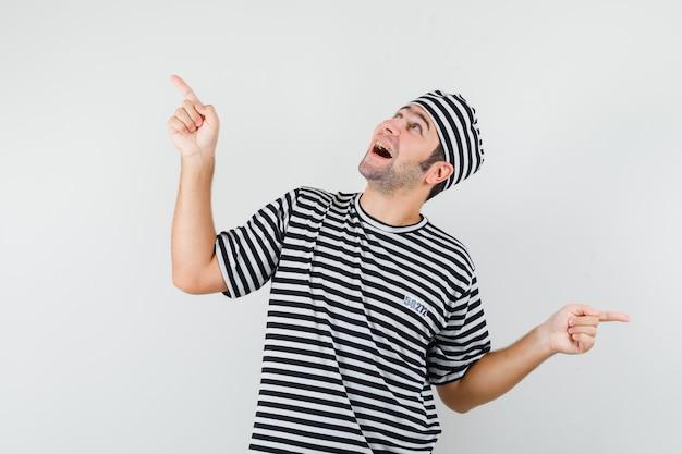 Varón joven apuntando hacia afuera en camiseta, sombrero y mirando feliz. vista frontal.
