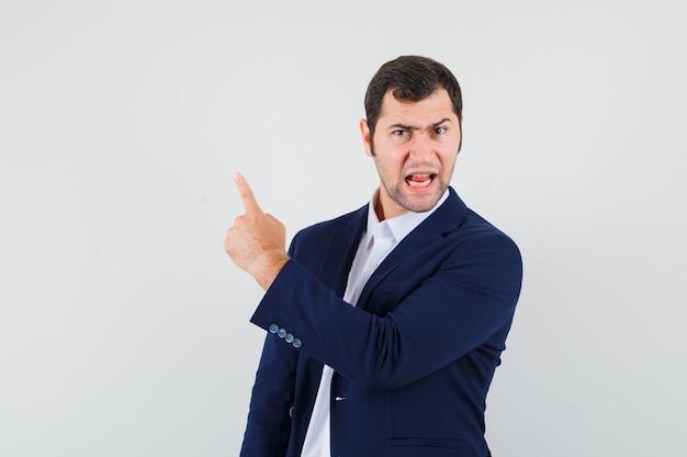 Varón joven apuntando hacia arriba en camisa, chaqueta y mirando enojado